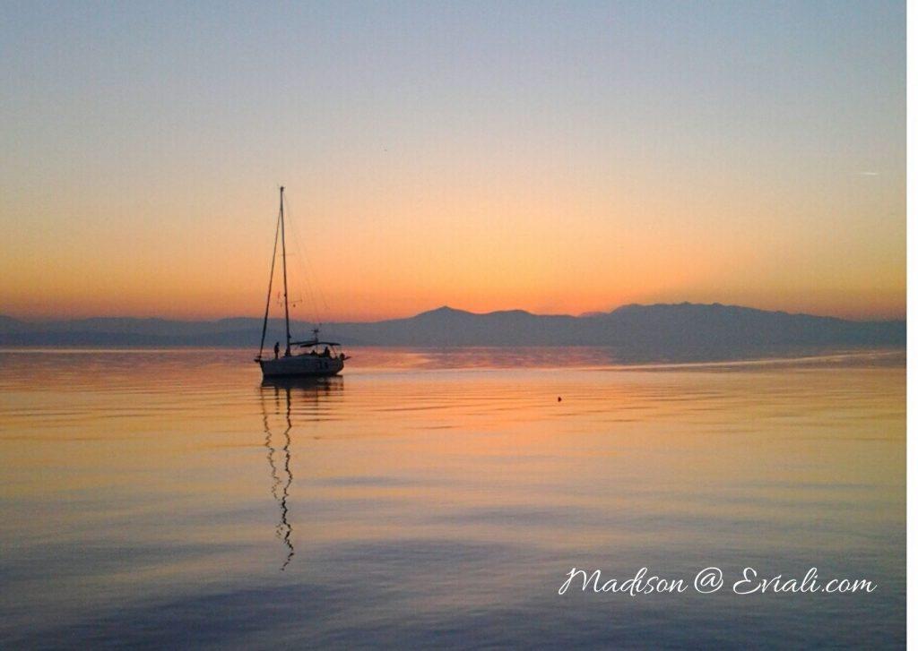 Sailing boat leaving Limni, Evia at Sunset